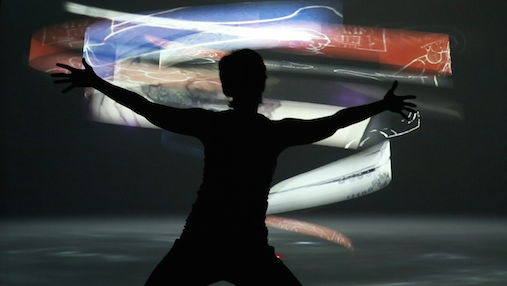 A dancer reaches her arms out in front of a colorful image vortex